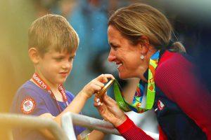 #25 Η ποδηλάτρια και μητέρα Κριστίν Άρμστρονγκ δείχνει το χρυσό μετάλλιο στον γιο της που κέρδισε στην ποδηλασία δρόμου γυναικών.