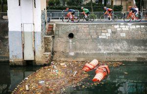 #23 Ποδηλάτες περνούν δίπλα από ένα υδάτινο φράγμα σκουπιδιών σε μολυσμένη γειτονία του Ριο.